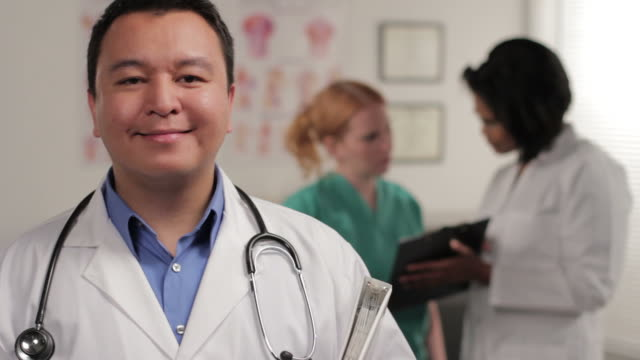 Confident male doctor, nurse in background video