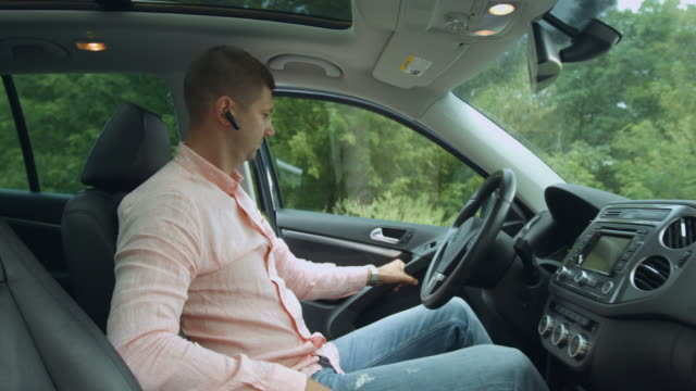 Confident male driver fastening seat belt in car Confident millennial entrepreneur with hands-free device closing car door, fastening seat belt before driving. Handsome male driver buckles up seat belt while sitting in car during business road trip. bluetooth stock videos & royalty-free footage