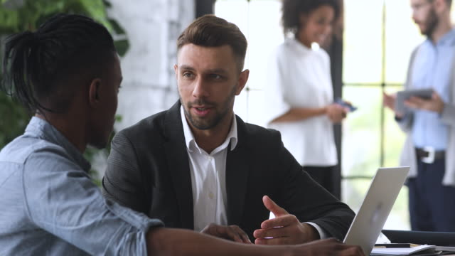 Confident male insurance broker manager consulting african client making offer