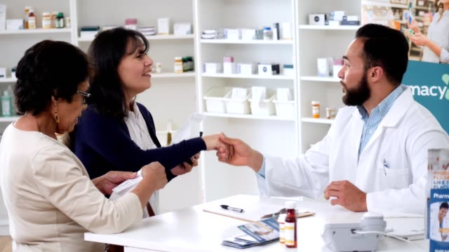 Confident male pharmacist assists female customers