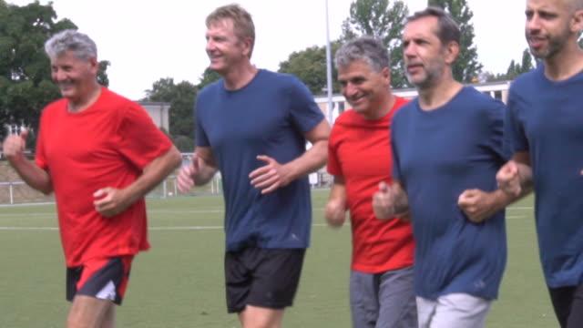 stockvideo's en b-roll-footage met vertrouwen mannelijke voetballers joggen op speelveld - voetbal teamsport