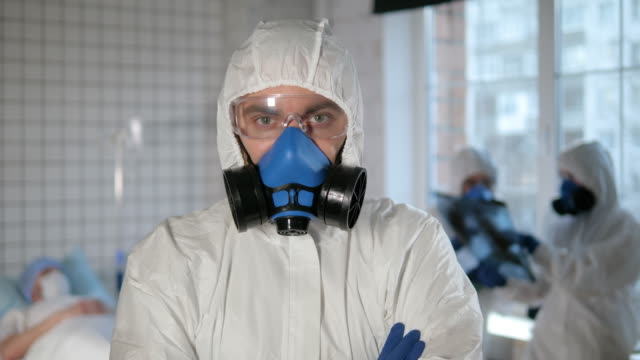 confident man in a biohazard suit folds hir arms and shows elements of his protection suit - hand on glass covid video stock e b–roll