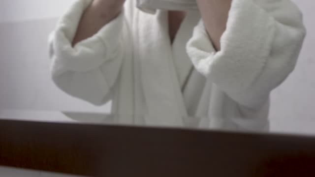 Confident man in white bathrobe wipes his face with a towel looking in the mirror in the bathroom.