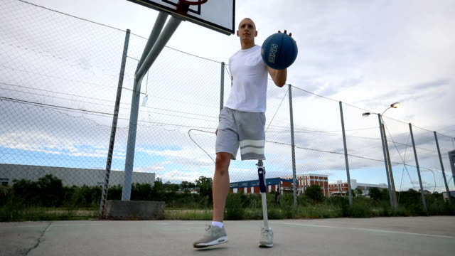 Confident man with artificial leg playing basketball Young amputee with a artificial leg, enjoying his time outdoors by playing basketball. artificial limb stock videos & royalty-free footage