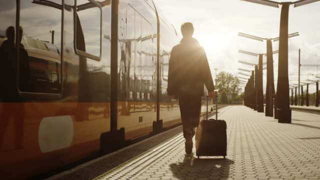 Confident Man With Luggage Walking on Railway Station at Sunset Time video