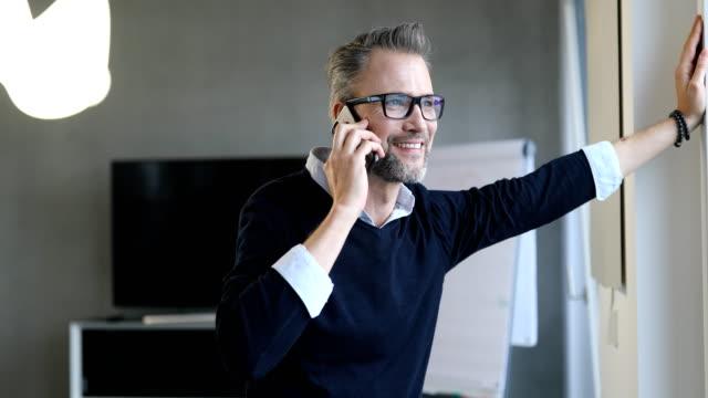 stockvideo's en b-roll-footage met vertrouwen manager communiceren via mobiele telefoon - gewone snelheid