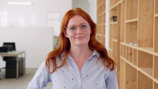 donna d'affari matura fiduciosa in ufficio creativo - capelli rossi video stock e b–roll