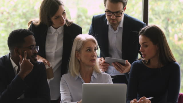 vídeos de stock e filmes b-roll de confident mature businesswoman showing project research results to teammates. - senior business woman tablet