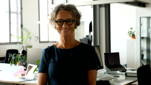 Confident mature businesswoman standing at office Panning shot of confident female entrepreneur standing at creative office. Portrait of smiling mature businesswoman is wearing eyeglasses at workplace. She is wearing smart casual. short hair stock videos & royalty-free footage