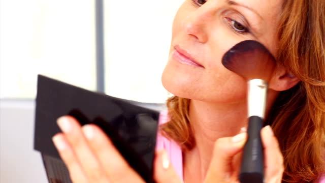 fiducioso matura donna applicare make up - femminilità video stock e b–roll