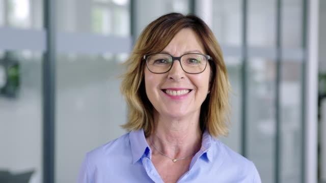 vídeos y material grabado en eventos de stock de mujer de negocios media adulta confiada en el cargo - sonrisa con dientes