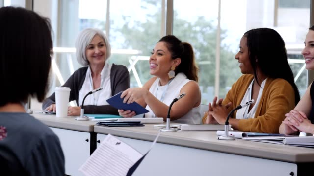 Confident mid adult Hispanic businesswoman encourages a group of women during a women's event