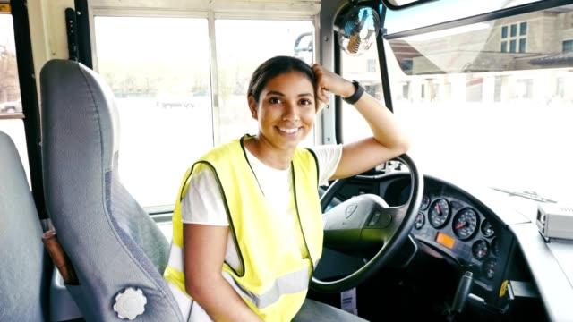 confident mid adult hispanic female school bus driver - autista mestiere video stock e b–roll