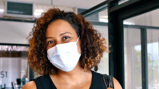confident mid adult hispanic woman wearing protective face mask during coronavirus pandemic - coprire video stock e b–roll