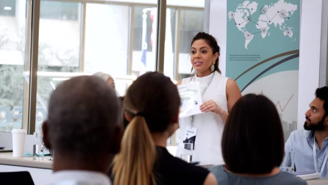Confident motivational speaker addresses businesspeople during conference Mid adult Hispanic businesswoman motivates colleagues while she discusses global business during conference. She shows them a world map while talking to the crowd of businesspeople. exhibition stock videos & royalty-free footage