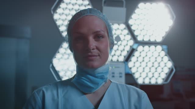vídeos de stock e filmes b-roll de confident nurse against illuminated surgical light - enfermeira