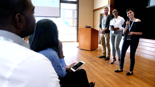 Confident panel of influencers answer questions during conference Diverse male and female millennial influencers answer questions during a Q and A portion of a conference. faq stock videos & royalty-free footage