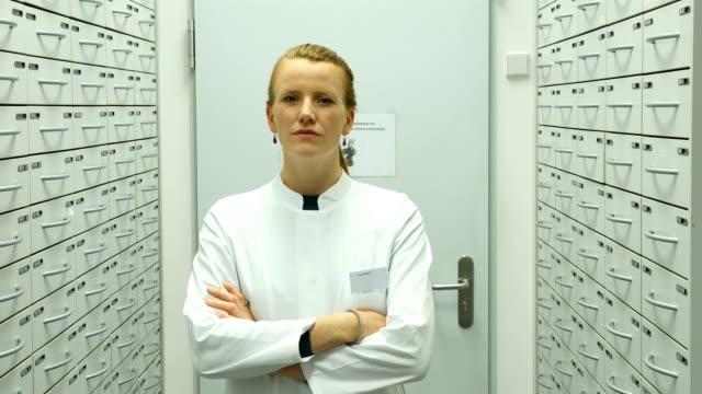 zuversichtlich apotheker lächelnd im lagerraum - wissenschaftlerin stock-videos und b-roll-filmmaterial
