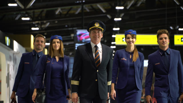 Confident pilot and cabin crew walking through airport ready to work video