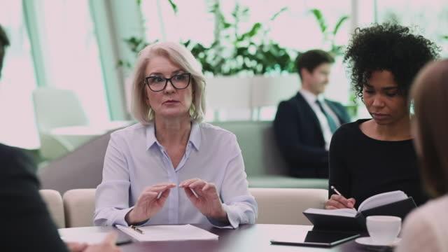 Confident professional mature businesswoman coach mentor teach diverse team people