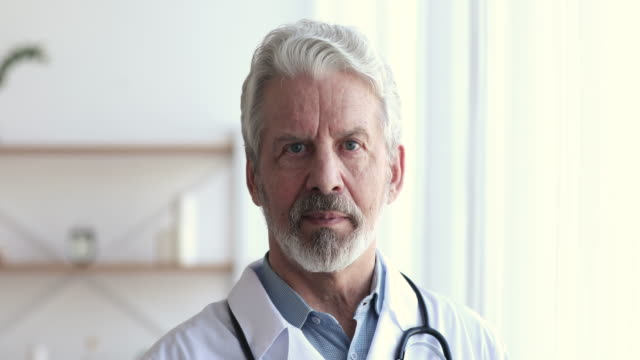 Confident professional senior male doctor looking at camera, closeup portrait Confident professional senior male doctor wearing white uniform, stethoscope looking at camera. Bearded 60s successful older man physician or gp with dental smile posing for close up face portrait. cardiologist stock videos & royalty-free footage