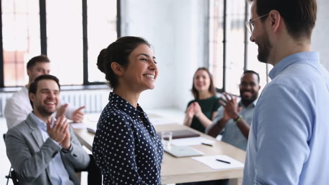 Confident proud indian employee of month handshaking company boss