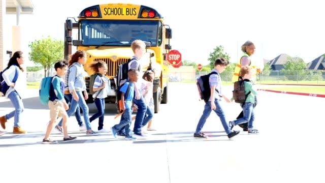Confident school crossing guard walks school children across the street video