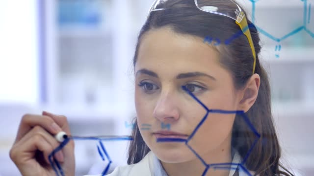 Confident scientist concentrates while drawing molecular structure on transparent board Young Caucasian female genetic research scientist concentrates while drawing molecular structure on transparent board. chemical formula stock videos & royalty-free footage