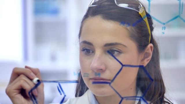 självsäker vetenskapsman koncentrat medan du ritar molekylstruktur transparent ombord - whiteboardtavla bildbanksvideor och videomaterial från bakom kulisserna