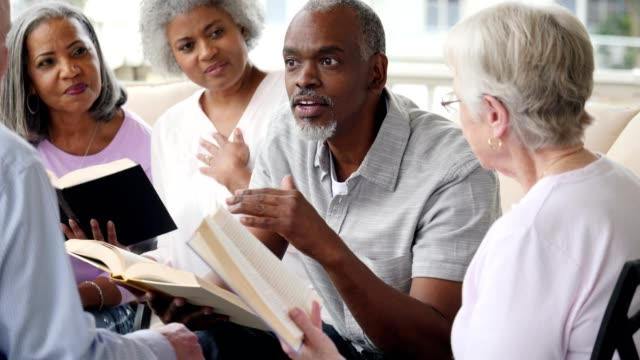 Confident senior African American man facilitates book club in retirement community