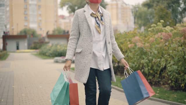 vídeos y material grabado en eventos de stock de mujer caucásica de confianza en covid máscara facial caminando con bolsas de compras en la ciudad. retrato de elegante comprador reatarte paseando sobre las ventas del viernes negro del coronavirus y saliendo. - black friday sale