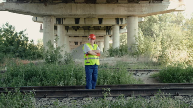 Confident senior railroader stands on railway and crossing hands at camera video