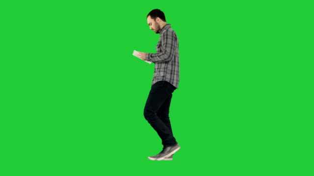 Confident serious man walking and working in tablet on a Green Screen, Chroma Key