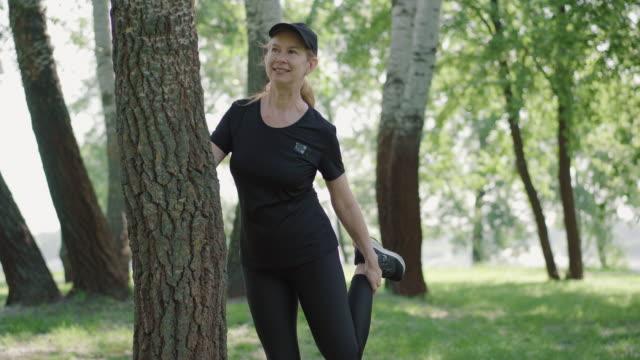 selbstbewusst lächelnde kaukasische sportlerin, die morgens im sonnigen park die beine streckt. porträt von schlanken positiven frau in sportbekleidung und mütze aufwärmen vor dem training im freien. sportkonzept. - einzelne frau über 30 stock-videos und b-roll-filmmaterial