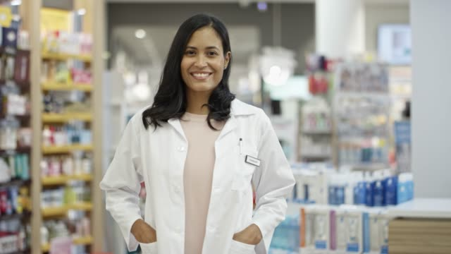 Confident smiling chemist with hands in pockets Panning shot of confident mid adult chemist with hands in pockets. Smiling female pharmacist standing in pharmacy. She is wearing lab coat. pharmacist stock videos & royalty-free footage
