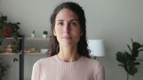 vidéos et rushes de femme de sourire confiant regardant l'appareil-photo restant au bureau à la maison - portrait