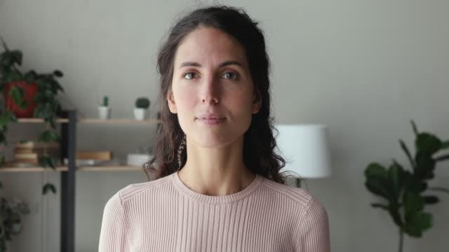 självsäker leende kvinna tittar på kameran står på hemmakontoret - mellan 30 och 40 bildbanksvideor och videomaterial från bakom kulisserna