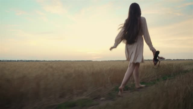 Confident smiling young european woman in light dress walking alone along yellow wheat barley field at sunset