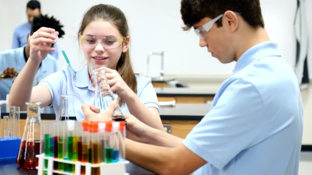 Confident STEM school students conducting chemistry experiment video