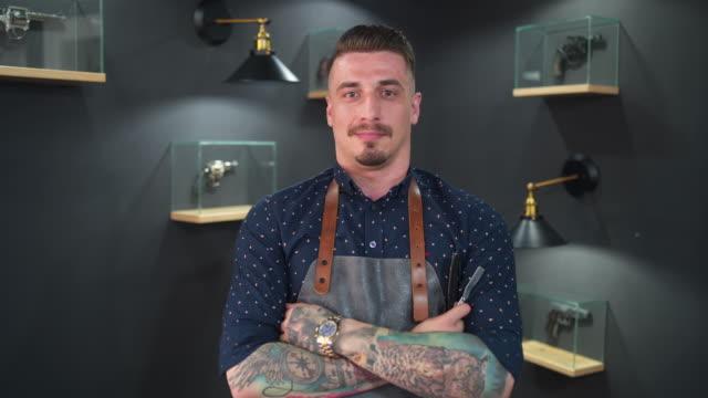 confident tattooed barber at his barber shop - tatuaż filmów i materiałów b-roll