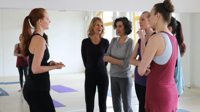 Confident trainer talking to women at yoga class video