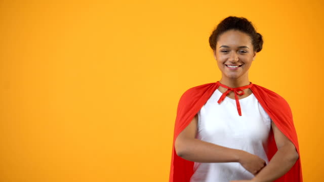 selbstbewusste frau im roten mantel stehen auf gelbem hintergrund, sicherheit, qualitätssicherung - held stock-videos und b-roll-filmmaterial