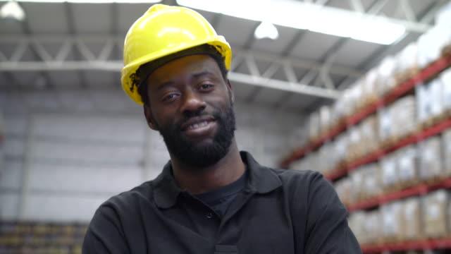 zuversichtlich arbeiter tragen helm im lager - bauarbeiterhelm stock-videos und b-roll-filmmaterial