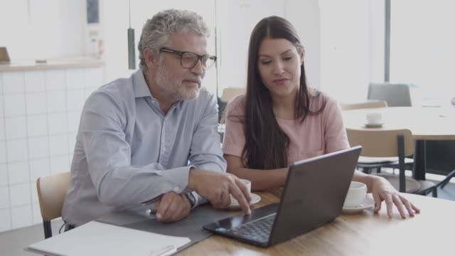 Confident workers in reading document via laptop, talking
