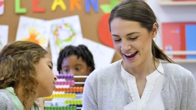 självsäker ung vuxen kvinnlig lärare frågesporter elementära skolflicka på math fakta - abakus bildbanksvideor och videomaterial från bakom kulisserna
