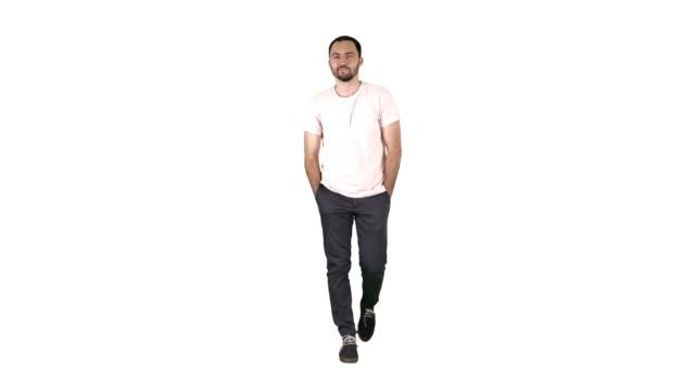 自信を持って若い大人の男が前方に歩いて白い背景に白いシャツでカメラを見て - 全身点の映像素材/bロール