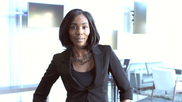 Confident young African-American businesswoman A confident young African-American businesswoman wearing a suit, standing in a business lounge, hands on her hips, looking at the camera. authority stock videos & royalty-free footage