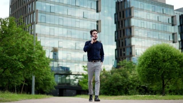 自信に満ちた若いビジネスマンがポケットに手を入れて街の通りを歩き、携帯電話で話す、スローモーションワイドショット - 全身点の映像素材/bロール