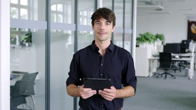 デジタルタブレットで自信を持つ若いビジネスマン - 上半身点の映像素材/bロール