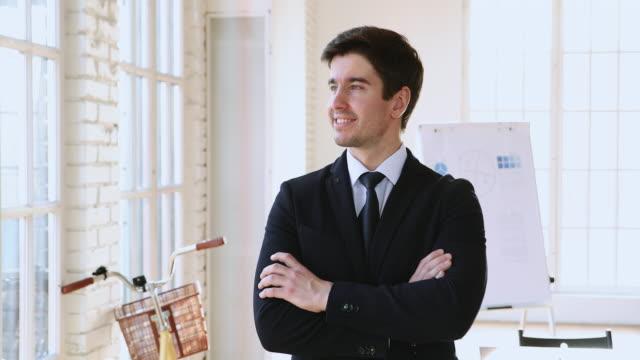 självsäker ung stilig affärsman i formellt slitage stående på arbetsplatsen. - formell klädsel bildbanksvideor och videomaterial från bakom kulisserna